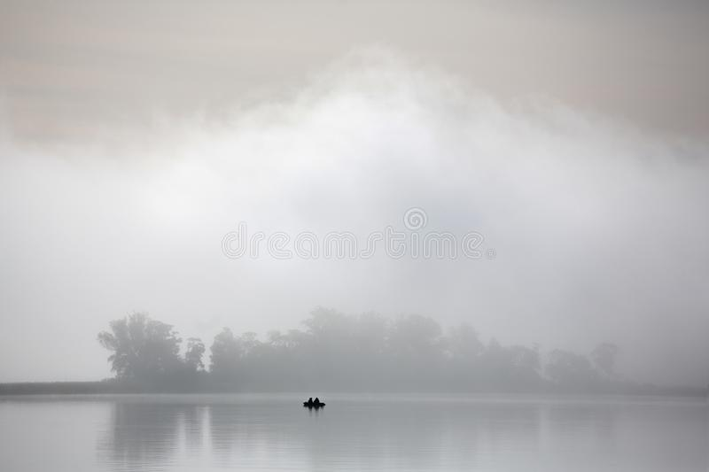 Misty autumn morning. Fishermen on the river in a boat royalty free stock photos
