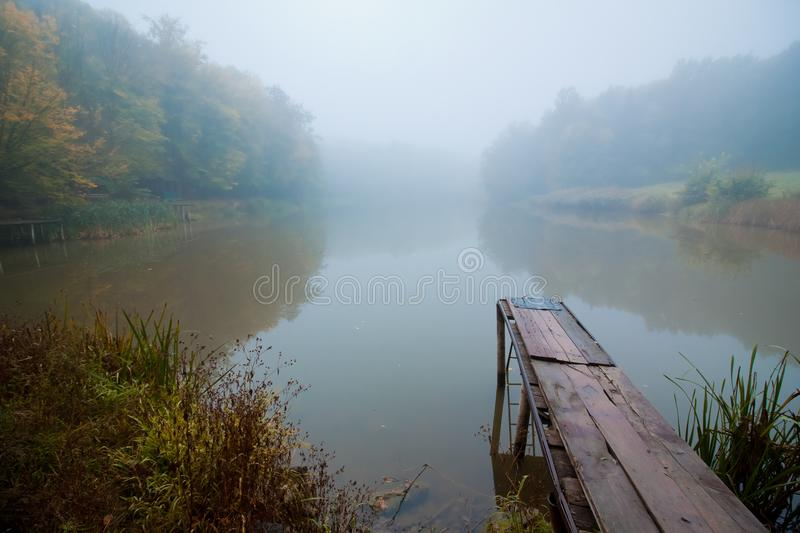 Misty autumn morning on a small lake, fog weather, wooden footbridge over still water surface, yellow trees reflections. Green countryside tourism concept stock image