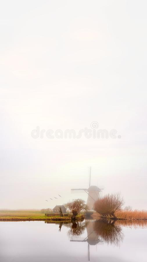 Misty and calm windmill sunrise stock photography
