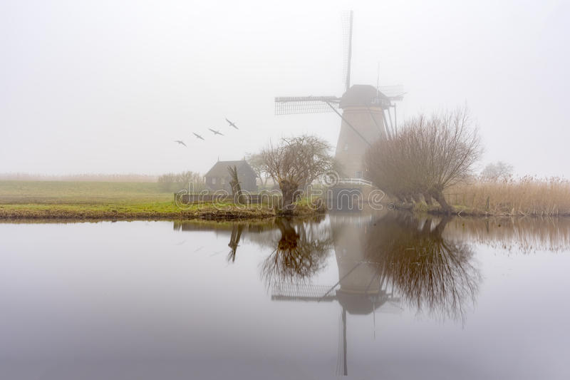 Misty and calm windmill sunrise stock image