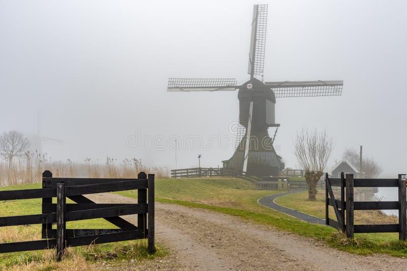 Misty and calm windmill sunrise stock photo