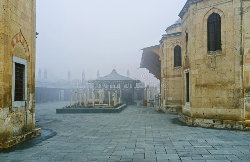 The misty cemetery. The misty view on the courtyard of Mevlana Museum with the silhouette of its beautiful sadirvan and medieval dervish cemetery, Konya, Turkey stock images