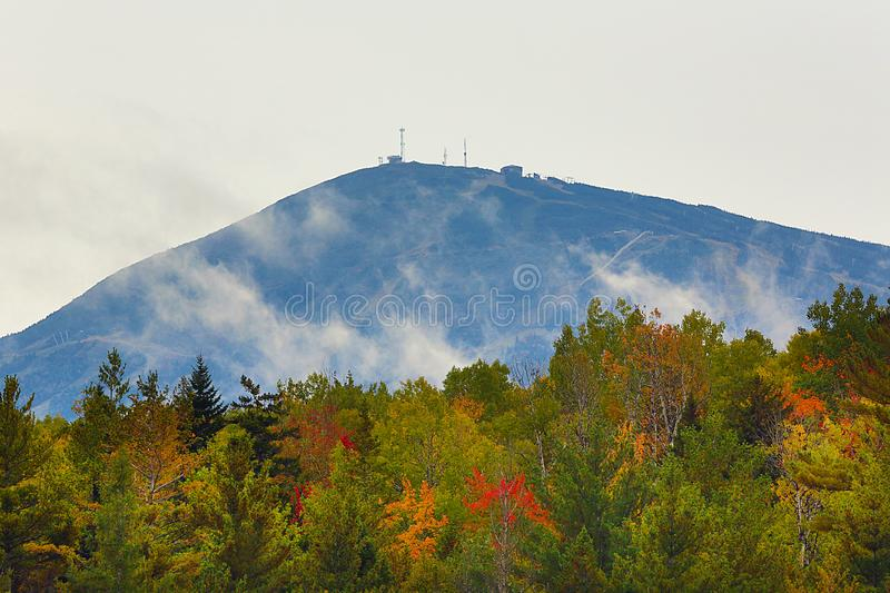 Misty clouds pass in front of Sugarloaf Mountain in Maine. Sugarloaf Mountain in Kingfield, Maine, with autumn colors on the shoreline of Stratton Brook Pond royalty free stock photo