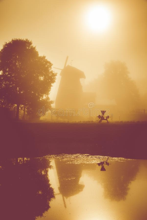Misty dawn near water, windmill stock images