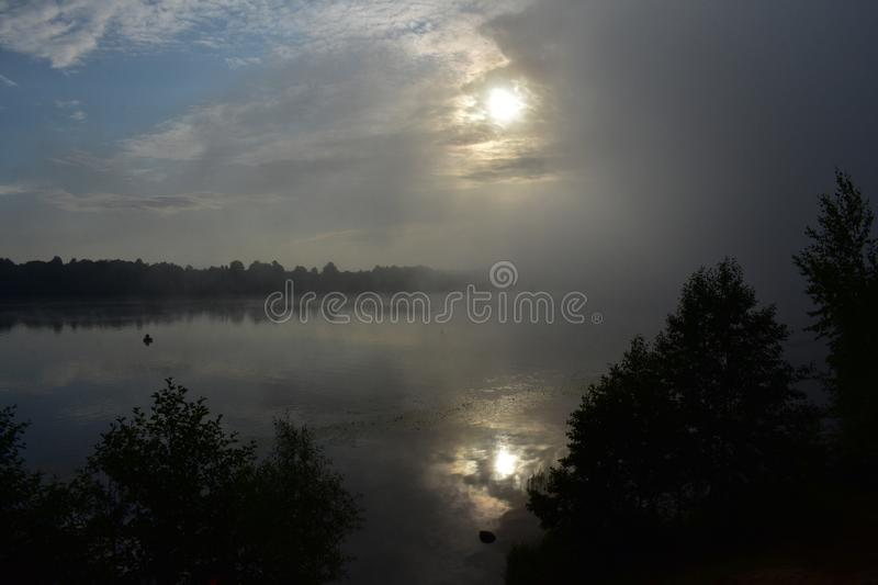 Misty dawn over the river, a lone fisherman in a boat, muddy outlines. The glare of shadows become clearer stock images