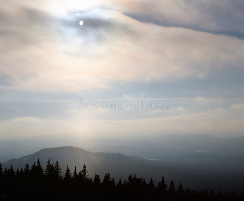 Misty evening of hilly area with ray of light. stock photography