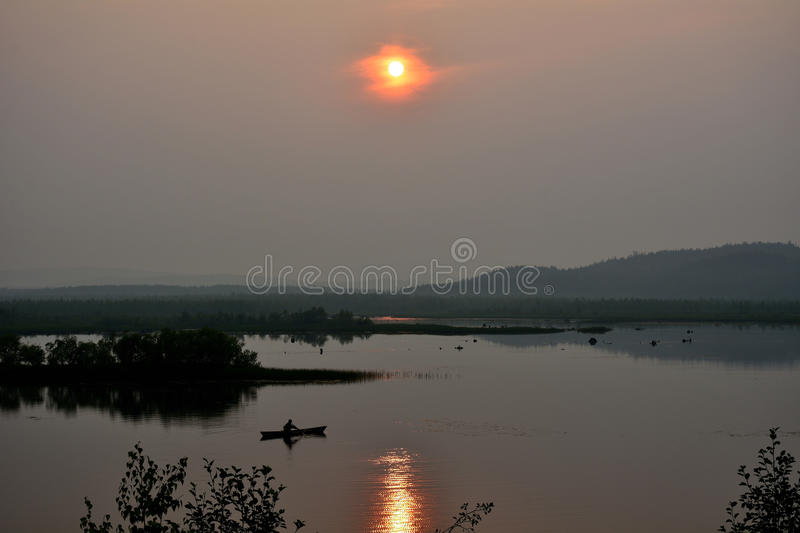 Misty evening on the lake with a fisherman in a boat with reflection of forest and sun royalty free stock images