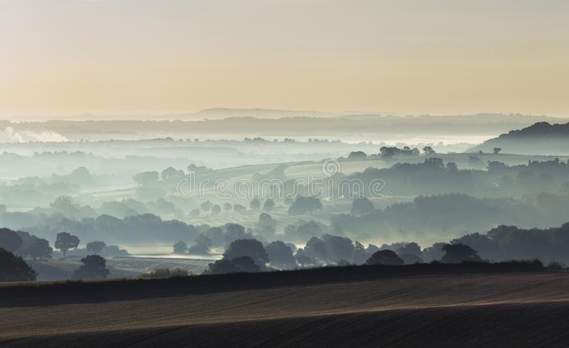Misty Fields of British Countryside at Early Autumn. British countryside rolling fields with trees in mist at autumnal morning. Shropshire in United Kingdom royalty free stock photo