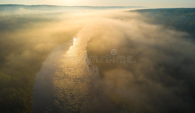 Misty foggy river with mst at sunrise. Orange yellow sun light stock photography
