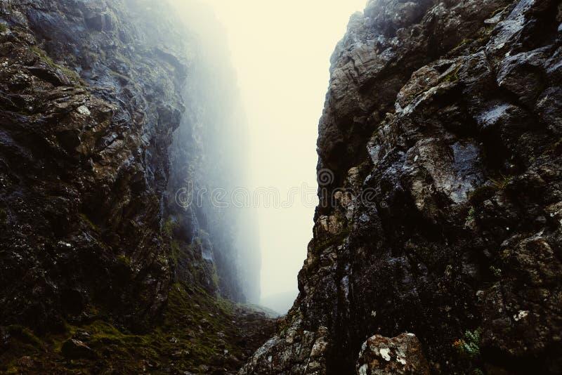 Misty gap between rocky cliffs royalty free stock image