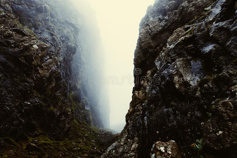 Misty gap between rocky cliffs royalty free stock image