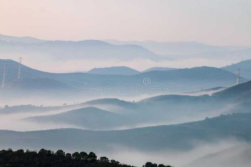 Misty hills in the morning. Beautiful view of the morning fog filling the valleys of smooth hills royalty free stock photos