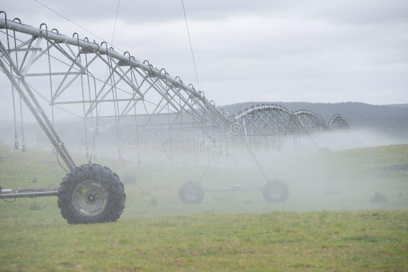 Misty Irrigation par l'arroseuse de pivot sur le champ d'herbe photos libres de droits