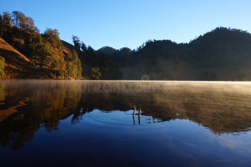 The Misty Lake of Ranu Kumbolo. The morning mist floated above the surface of the lake of Ranu Kumbolo, the beautiful lake inside of Bromo Tengger Semeru stock image