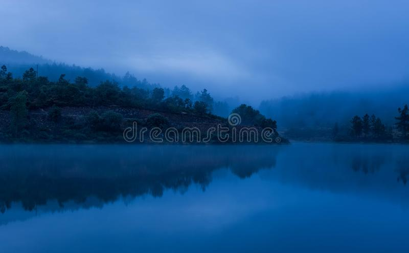Misty lake with reflections and forest stock image
