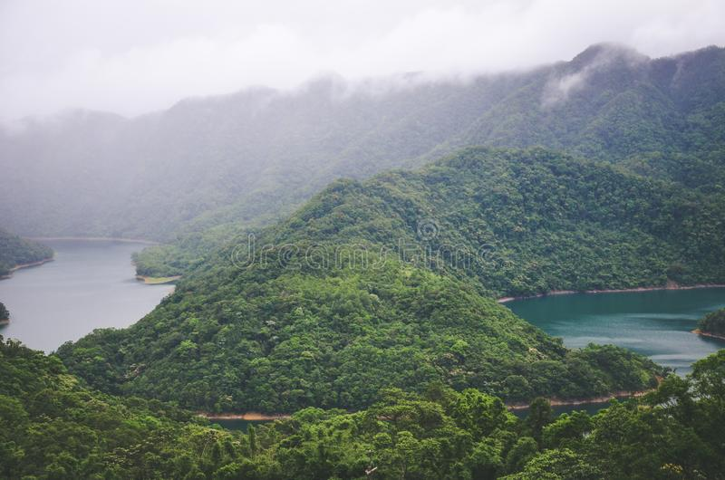 Misty landscape by Thousand Island Lake in Taiwan, Asia. Lake in fog surrounded by tropical forest, rainforest. Moody weather. stock photography
