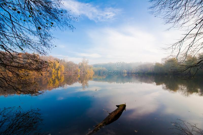 Misty late autumn morning, sleepy natural lake enjoys first sun rays getting through tree branches, attractive tourist sightseeing stock photo