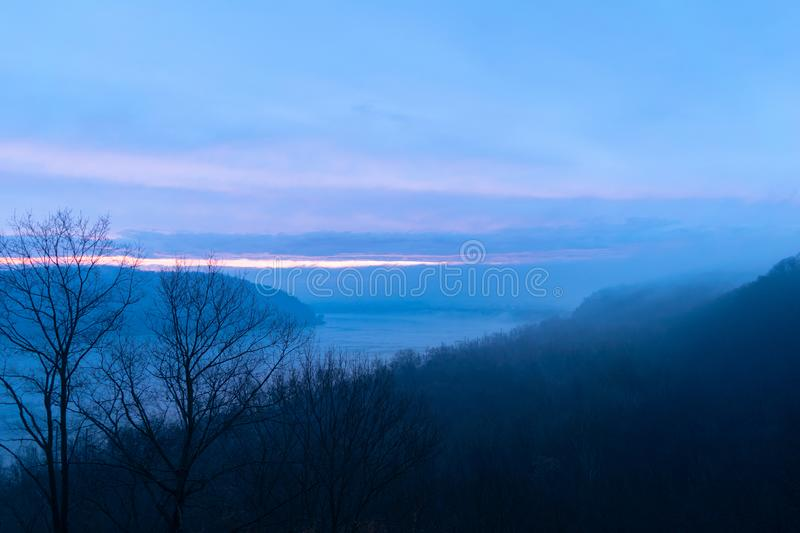 Misty and moody shot of a bend in the Susquehanna River, while a sliver of sunset breaks through the thick clouds. Misty and moody shot of a bend in the stock images