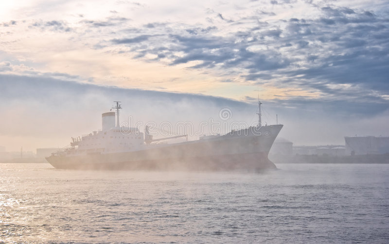 Misty morning. Ship passing by on a misty autumn morning at sunrise royalty free stock images