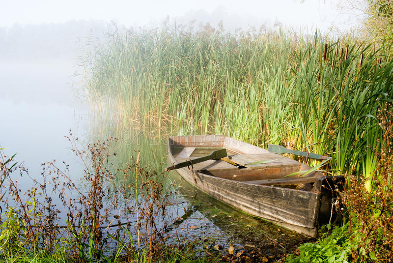 Misty Morning and A Boat. Misty morning at lake, rowing boat royalty free stock photo