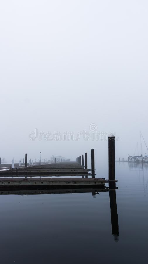 Harbor and boating docks on a misty morning. Misty morning empty boating docks on glassy-still waters and foggy skies stock images