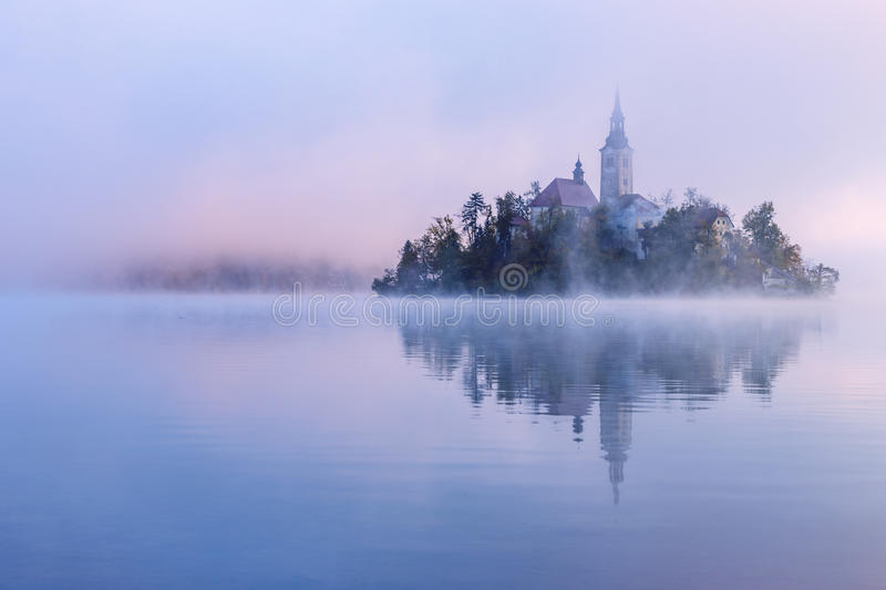 Misty morning in lake Bled. And famous island with old church-Slovenia stock photography