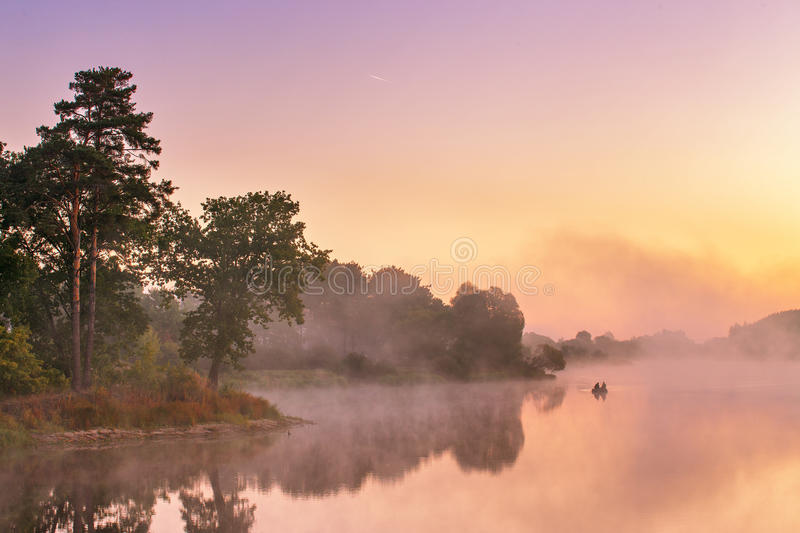 Misty morning on the lake. Fishing boat at a foggy river royalty free stock images