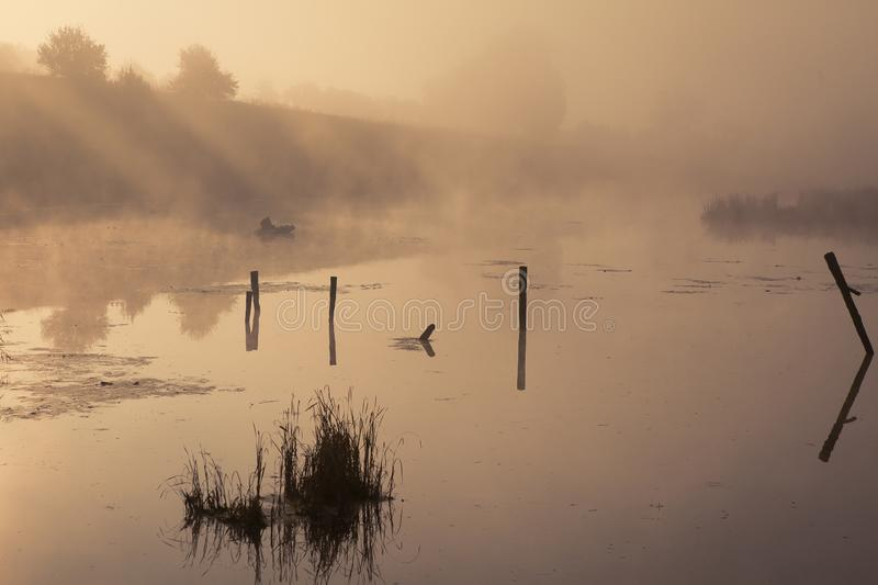 A misty morning by the lake. Small fishing boat at the lake. stock photos