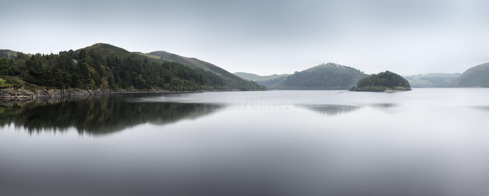 Misty morning landscape panorama over calm lake in Autumn royalty free stock photo
