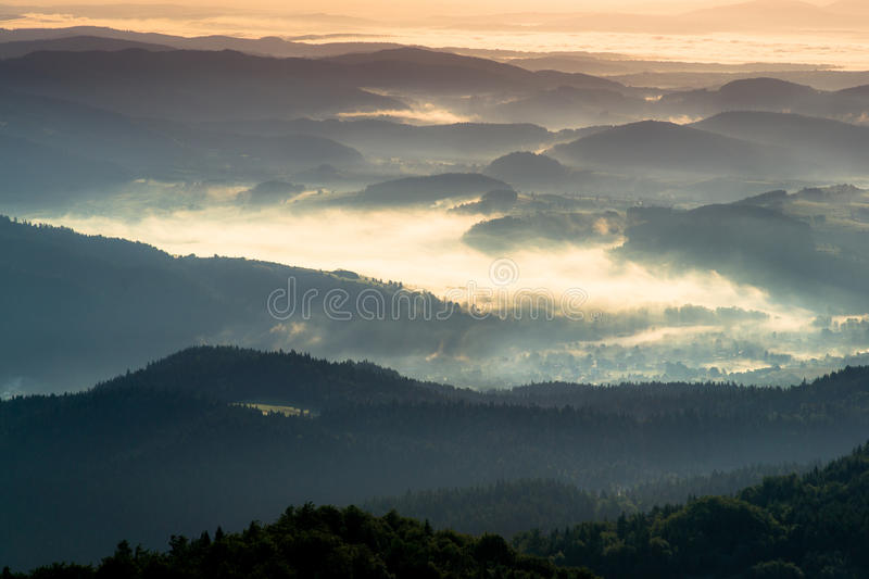 Misty morning in mountains. View from the top of Gorc peak on Gorce Mountains and Beskid Sadecki hills in morning fog stock image