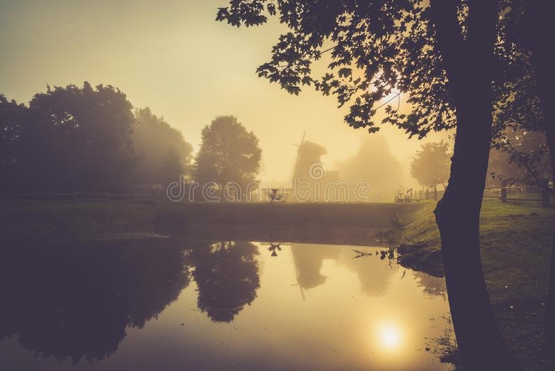 Misty morning near water and forest reflection. Misty morning after a rain near water and forest reflection on lake, countryside view, old wind mill on the stock images