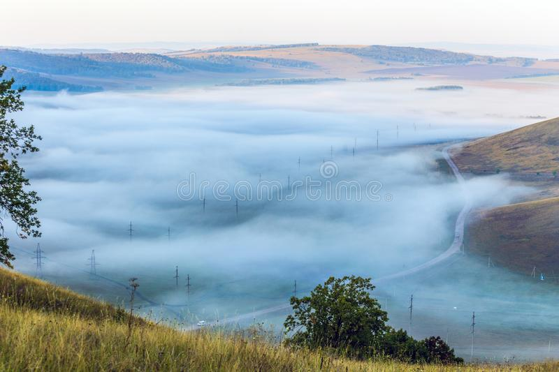 Misty morning over the valley in the Ural mountains. View through the thick fog on the valley in the Ural mountains stock photography