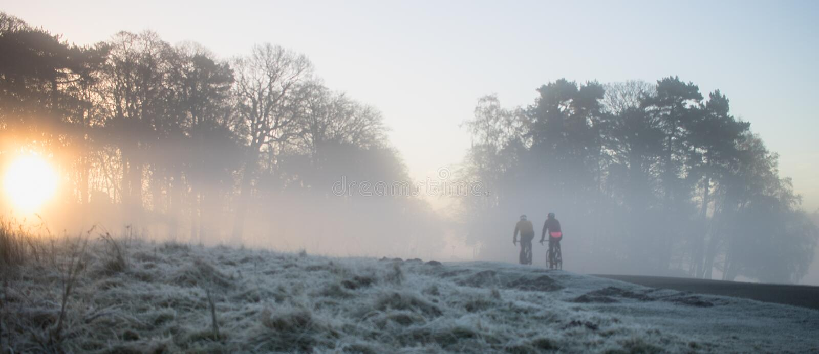 Misty morning ride. Two hardy cyclists brave a cold and frosty ride. The rising sun can be seen braking though a group of trees. A misty and atmospheric seen royalty free stock image