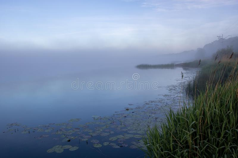 A misty morning by the river. A misty autumn morning by the river in different shades of blue stock images