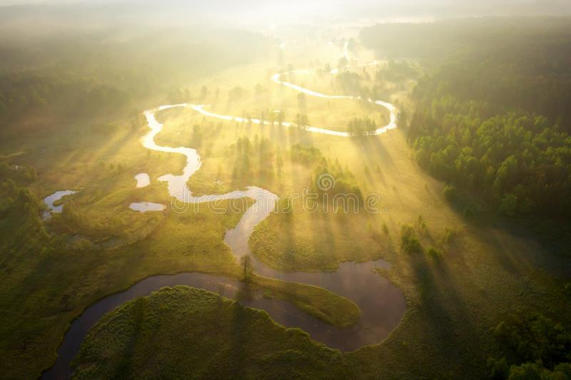 Misty morning river in sunlight. River landscape aerial view. Riverside view from above. Summer nature in sun rays. Drone view on royalty free stock photos