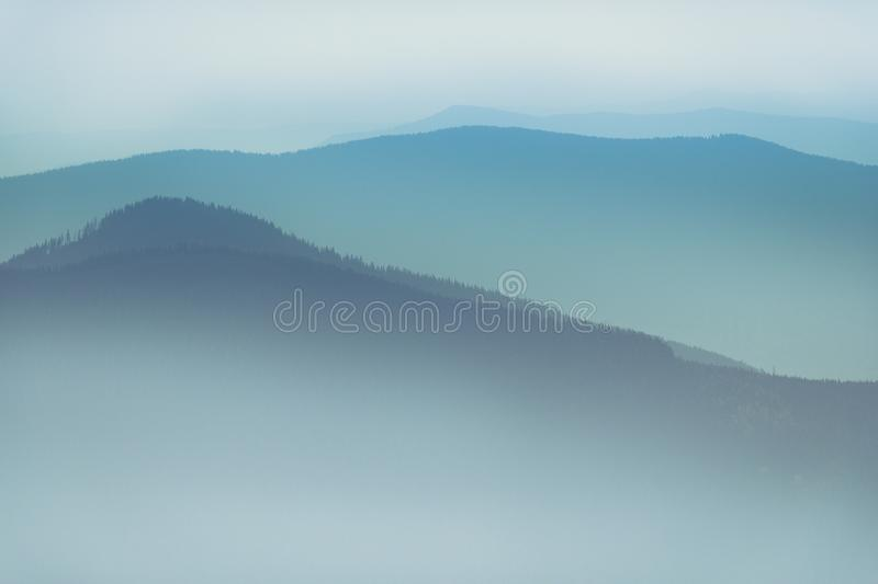 Misty mountain hills landscape. View of layers of mountains and haze in the valleys. stock image