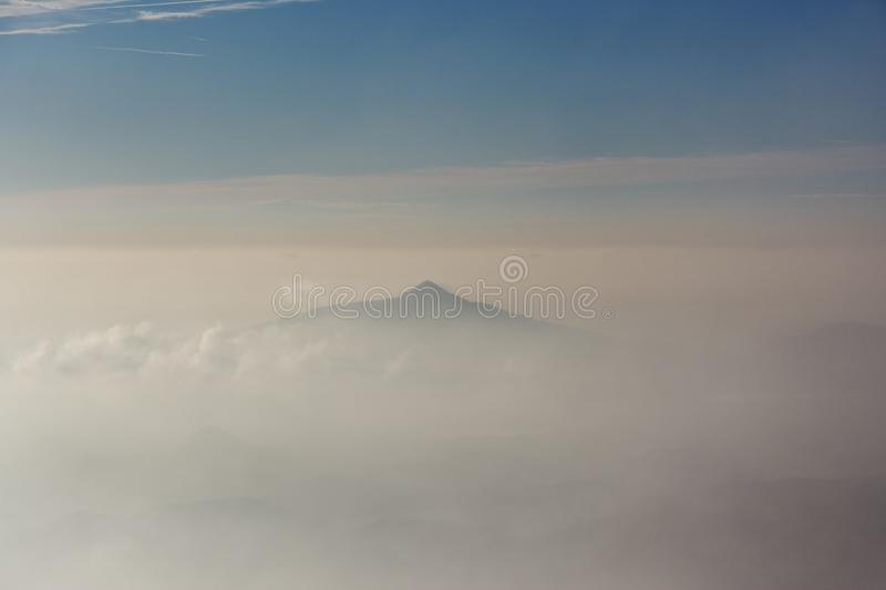 Misty mountain peaks over the clouds. Misty mountain peaks peeping over the clouds during sunset royalty free stock photography