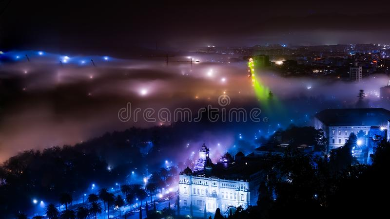 Misty night view in Malaga city with crane and ferris whele. Spain royalty free stock photo