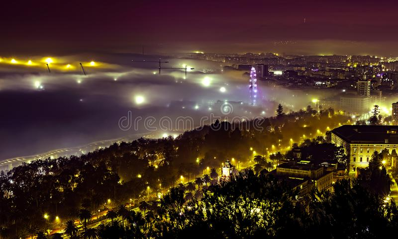 Misty night view in Malaga city with crane and ferris whele, Spain. Aerial view stock photo