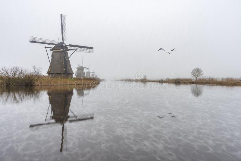 Misty and rainy windmill sunrise stock photography