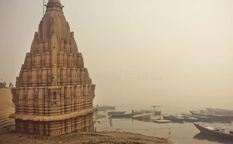 Misty scene of Ganges riverbank and sacred flooded Shiva temple in Varanasi. India. Historical landscape at morning stock photography