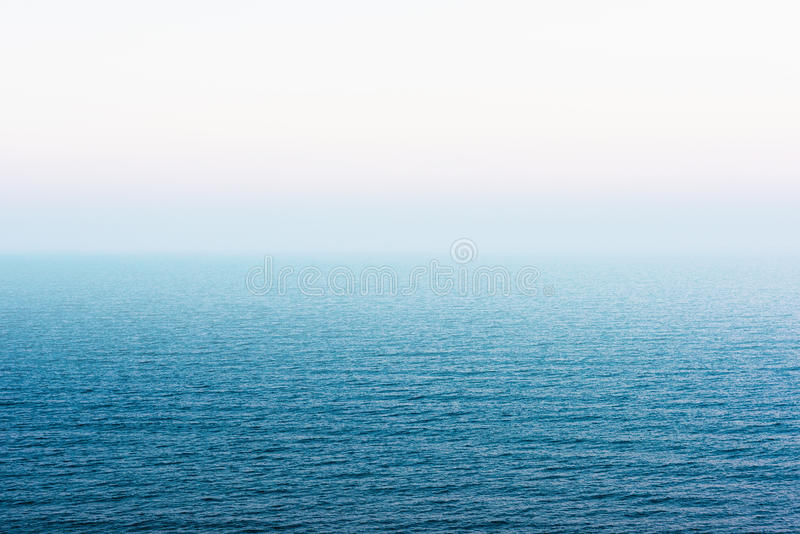 Misty sea. Foggy sea. Blue water and white clouded skies background royalty free stock image