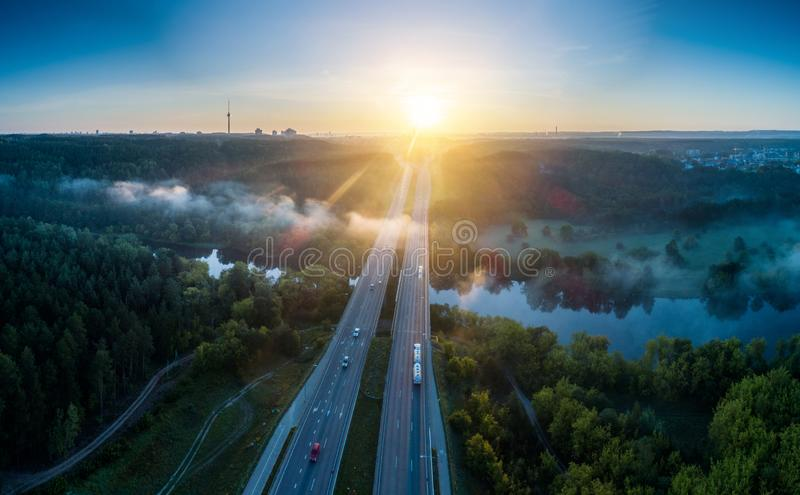 Misty sunrise landscape of road and river near town. Scenic nature near industry royalty free stock photography