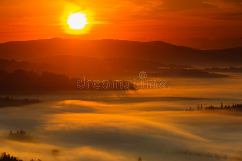 Misty sunrise in mountains in Koniaków stock images