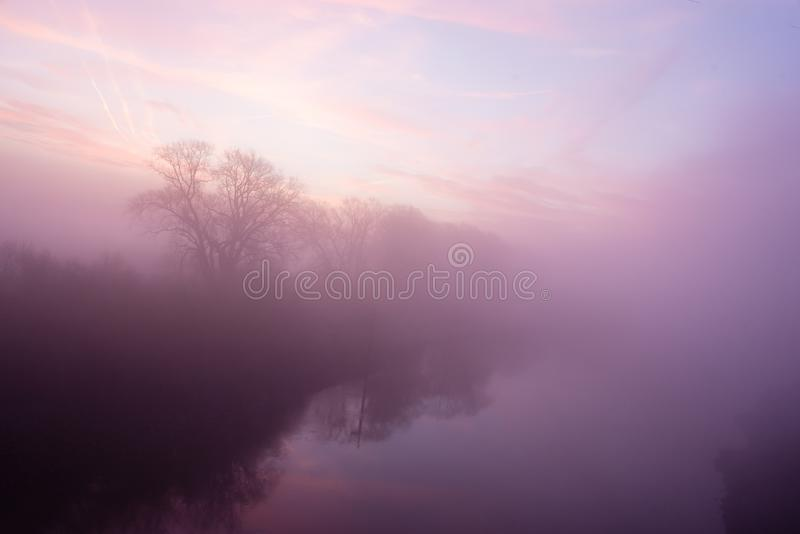 Misty sunrise over a river. Misty sunrise over a Belgian river with soft pastel colors stock photos