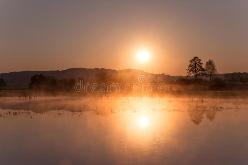Misty Sunrise Reflecting au-dessus de lac Mauensee au printemps image stock