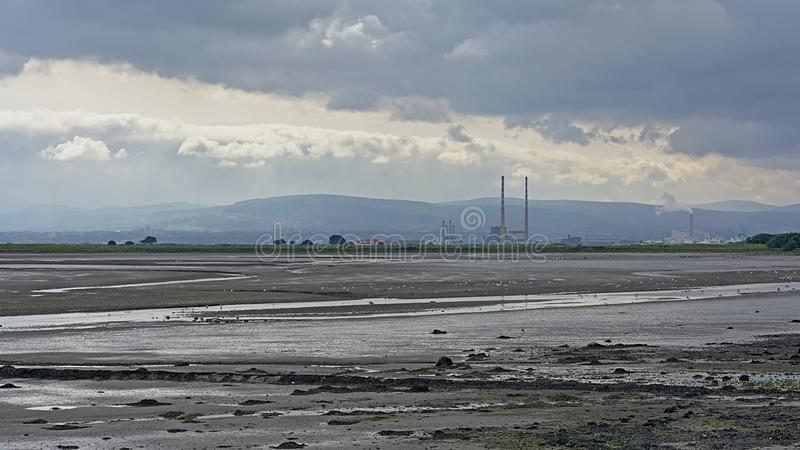 Misty view from across the water on Poolberg peninsula, with the chimneys of the power generation station , view from the beach royalty free stock images