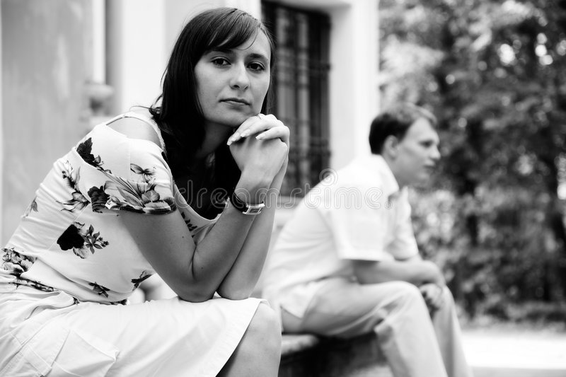 Misunderstanding. Black and white shot of young sad woman and man sitting on marble steps in park, selective focus royalty free stock images