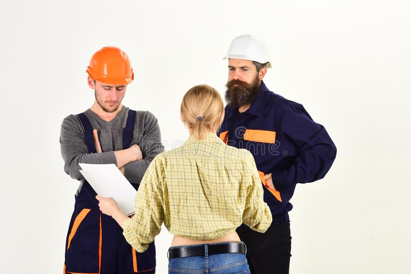 Misunderstanding concept. Brigade of workers, builders in helmets, repairers, lady arguing, discussing contract, white royalty free stock images