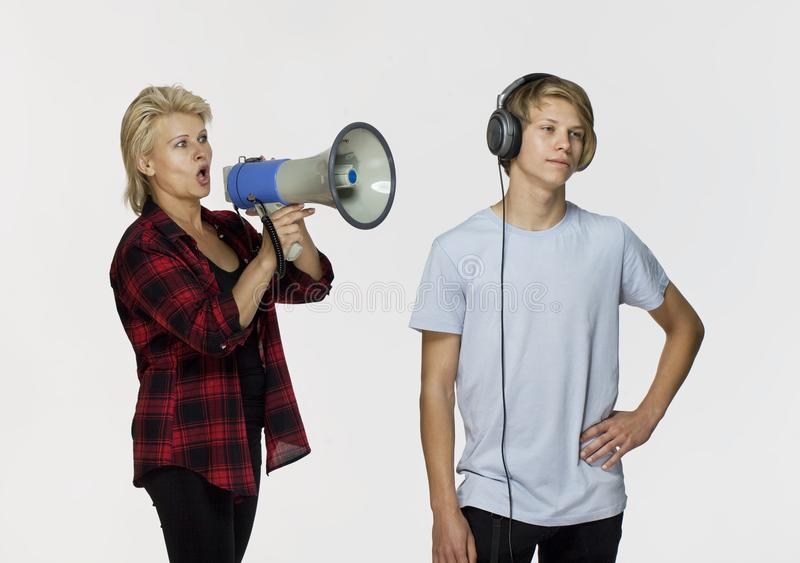 Generation gap. Male teenager not talking after an argument. Misunderstandings in family. Angry mother with megaphone talking to her male teenager stock images